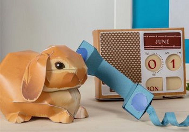 A 3D paper rabbit, talking on a paper telephone, with a paper radio in the background.