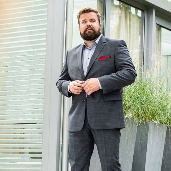 A bearded man stands in front of a windowed building, wearing a grey suit, blue shirt and has a red pocket square. There is a green plant to his right.