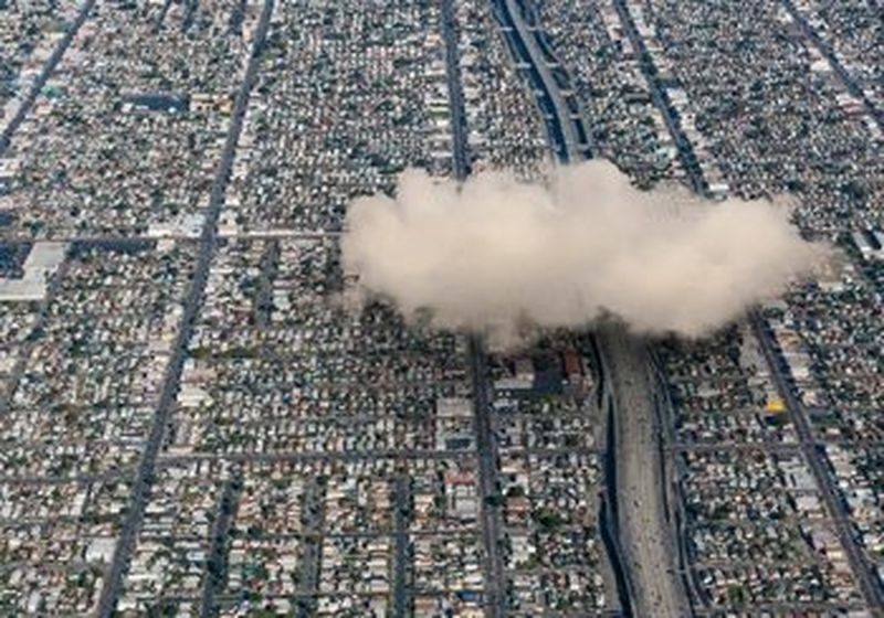 An aerial view of a city with a large white fluffy cloud above it on the right-hand side.
