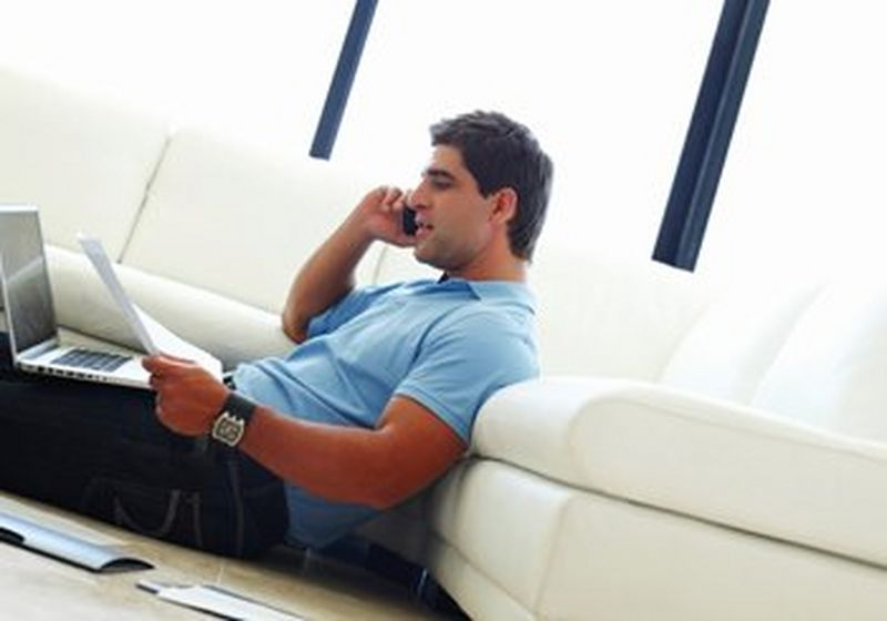 A man, clearly working from home with a laptop on his lap, speaking on a mobile phone.