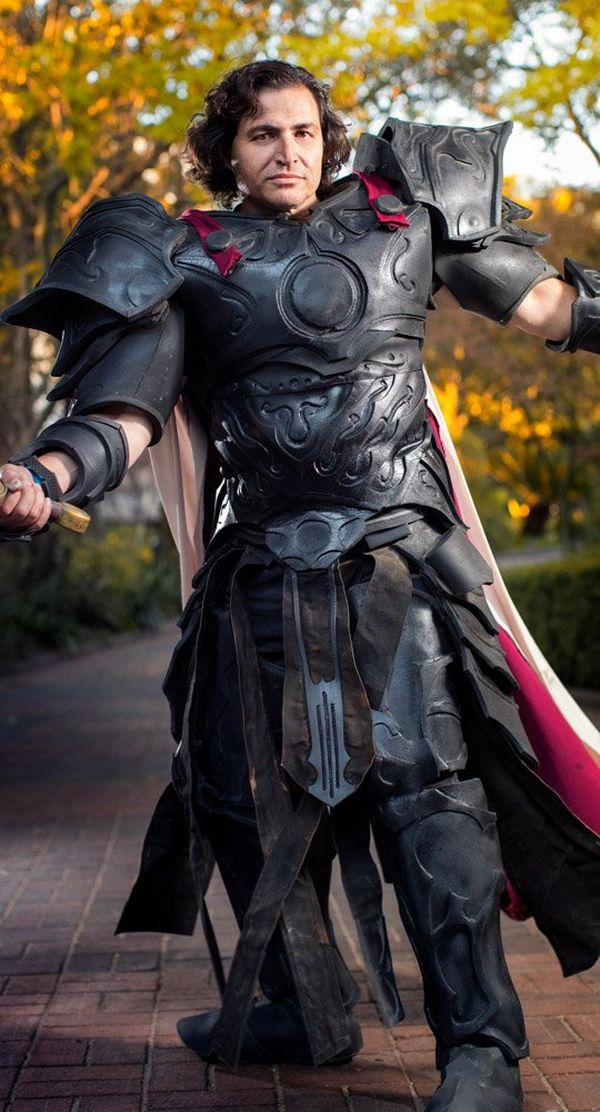 A man in cosplay costume poses in a park.