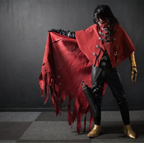 A cosplayer stands against a dark background, face covered, lifting a red cape.