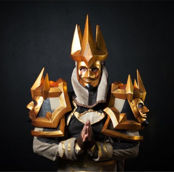 An elaborate costume of gold and silver, with gold masks as epaulets. The cosplayer stands with hands on prayer position.