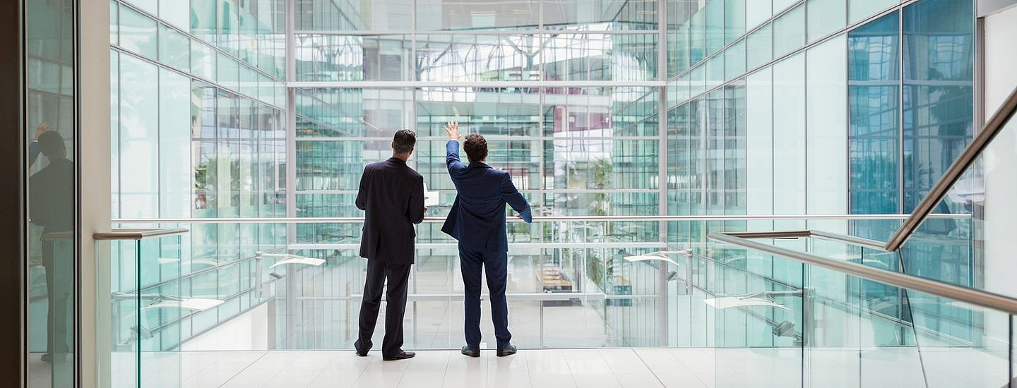 Two suited men with their backs to the camera gaze out through a large glass office building, with one pointing upwards.