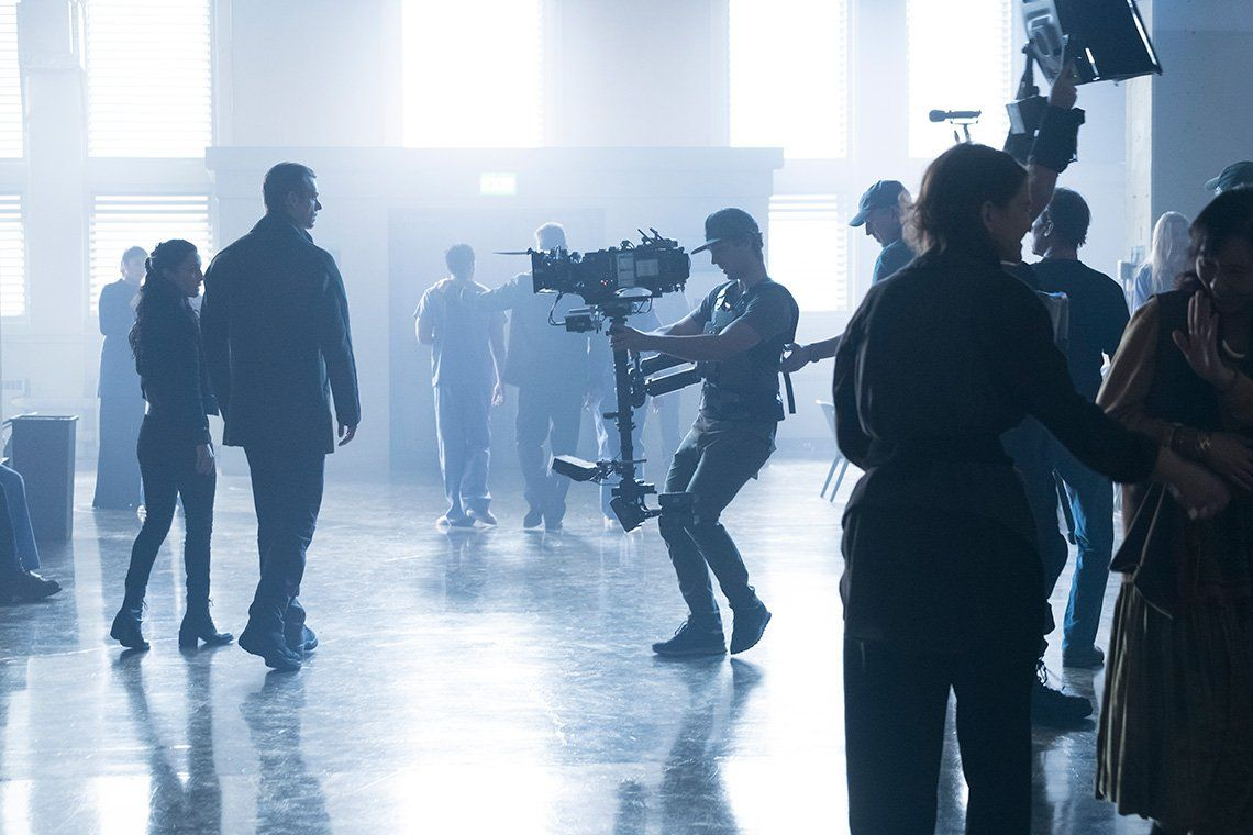 Two actors walk in a light-filled room, being filmed for Altered Carbon.