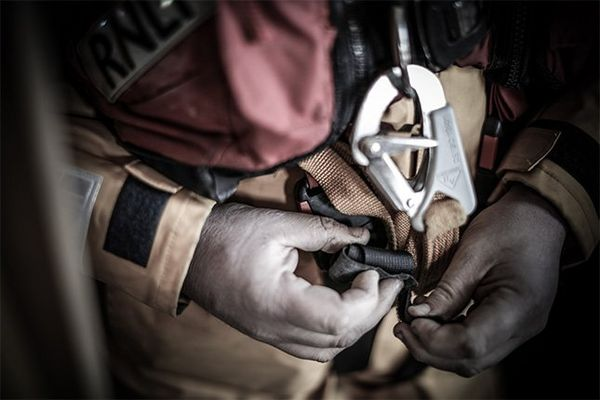 A close-up shows a volunteer's hands fastening a harness over their yellow sailing gear and red life vest.