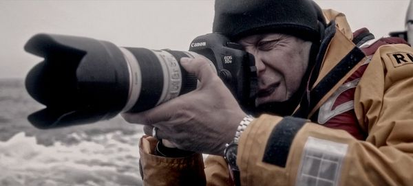 Photographer Clive Booth holds a Canon EOS 5DS with a long Canon lens.