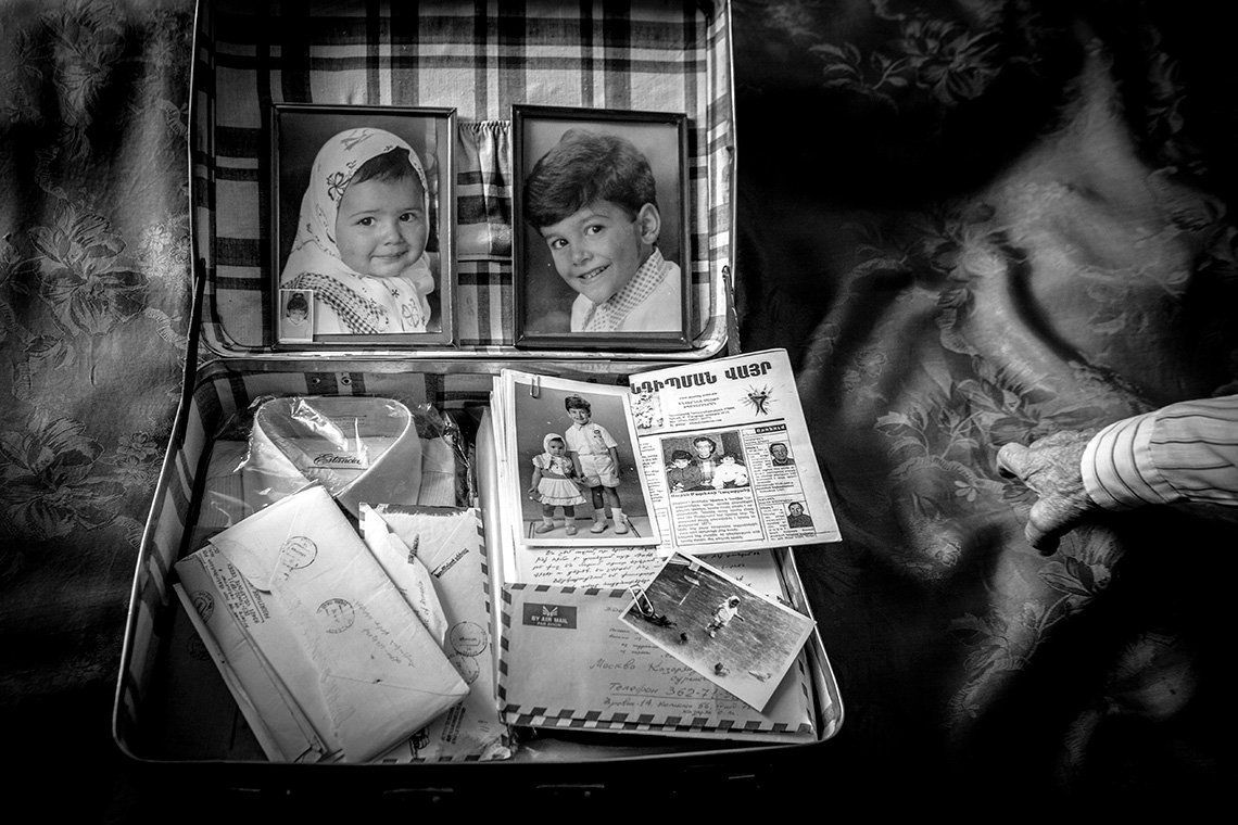 Inside a suitcase lid are photos of a young girl and boy. In the main suitcase is a shirt still in its plastic packaging, newspapers, letters and another photo of the children.