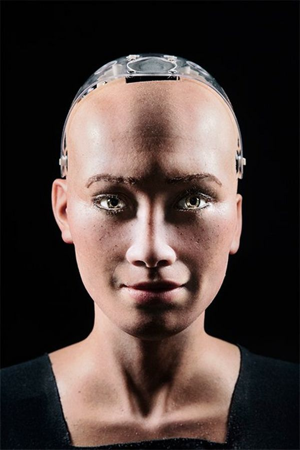 A close-up portrait of Sophia's face and shoulders, with her smiling slightly and her robot skull exposed slightly on top, shot against a black background.