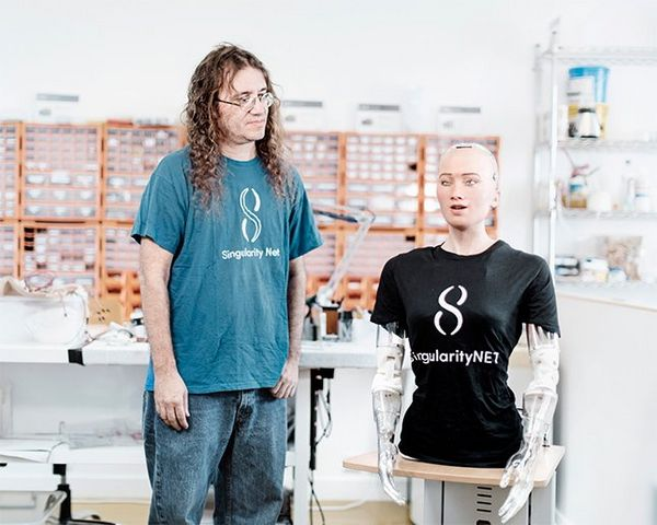 Dr Ben Goertzel stands beside Sophia's head and torso, which sits on a plinth in a workroom with shelves and drawers of parts and tools on the walls and tables. Both wear T-shirts bearing SingularityNET's logo.