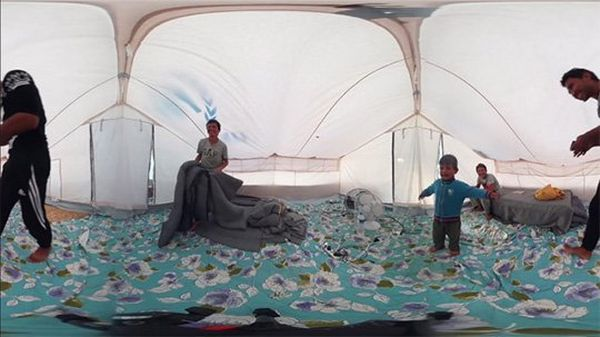 A still image from a 360-degree VR camera shows the inside of a tent with a turquoise floral rug, teenagers and a young child.