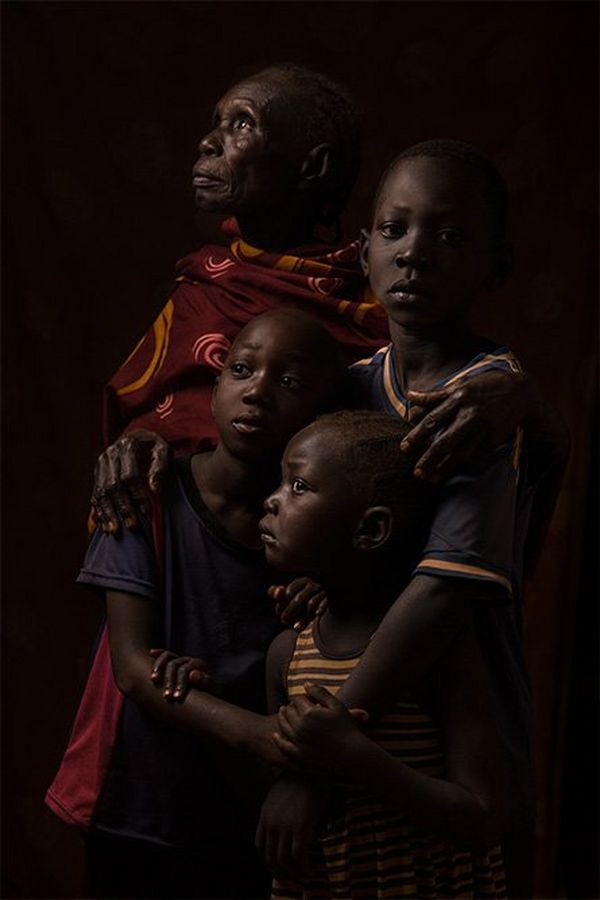 An African grandmother stands with her three grandsons in front of a dark background.