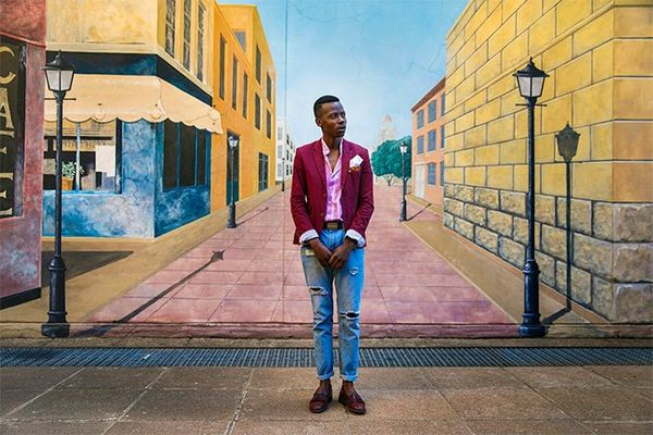 South African fashion blogger Ofentse Lewis wears a red blazer and jeans and stands in front of a painted mural showing a smart street scene.