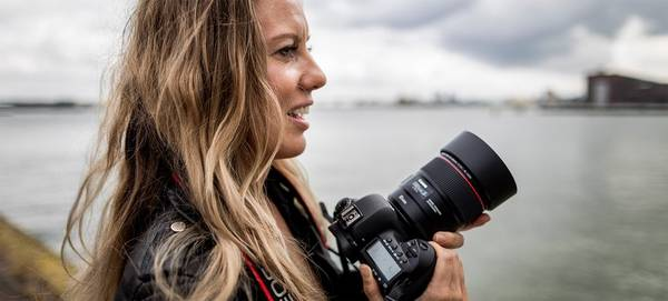 Photographer Ilvy Njiokiktjien stands in front of a harbour holding a Canon DSLR.