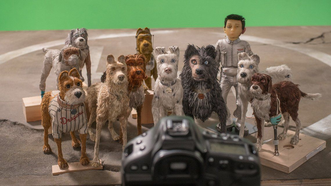 Dog puppets and an astronaut puppet are positioned in a group in front of a green screen, with a Canon EOS-1D X DSLR pointed at them to take their picture.