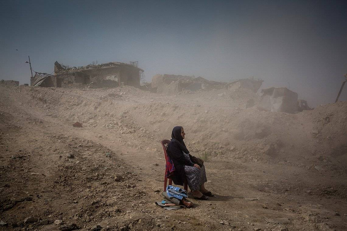 An elderly Iraqi lady sits on a dining chair in the middle of a dusty rural road with collapsed houses at the side.
