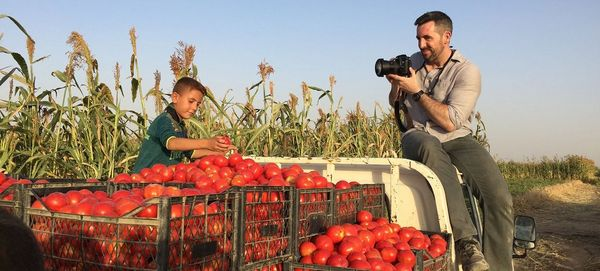 Photojournalist Ivor Prickett sits on the roof of a truck to take a picture of a boy sorting crates of tomatoes.