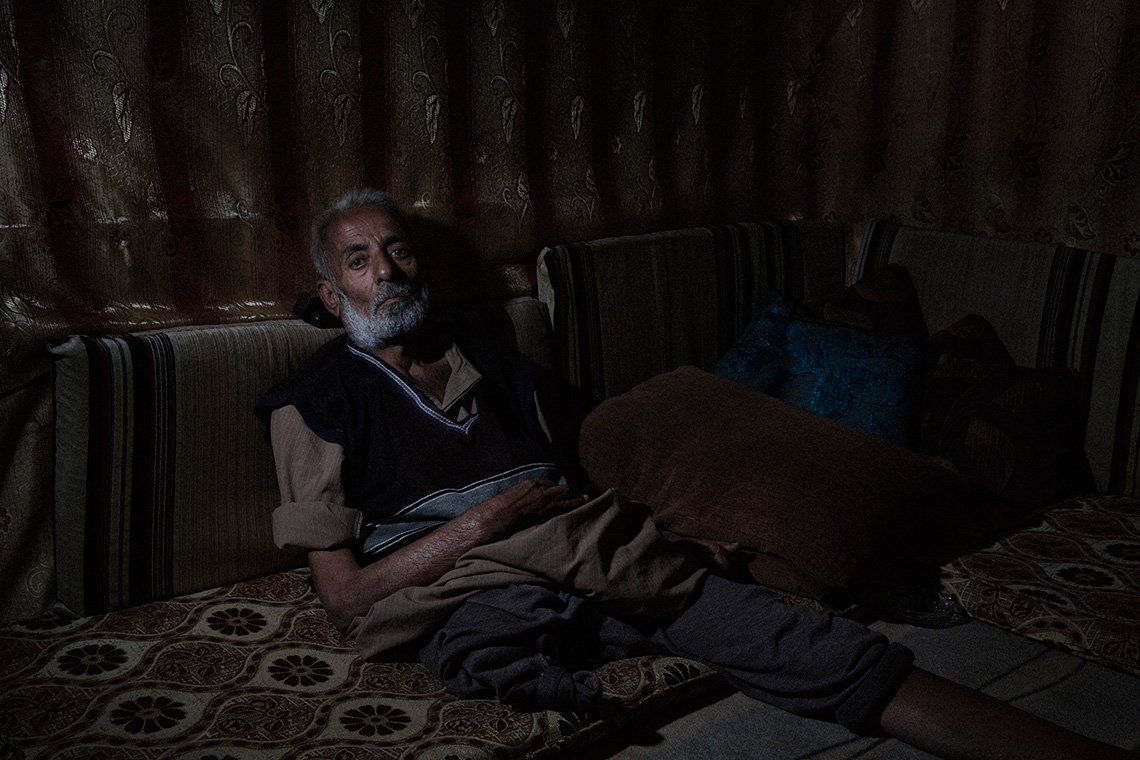 A man who has lost one legs leans against some cushions in a shabby makeshift tent in Lebanon.
