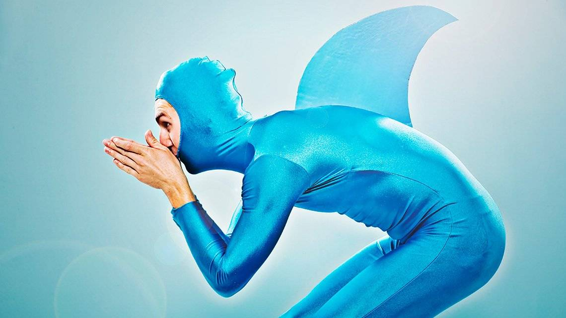A man wears a shiny, metallic blue all-in-one outfit with a head covering and a shark fin on his back. He is poised as if to dive.