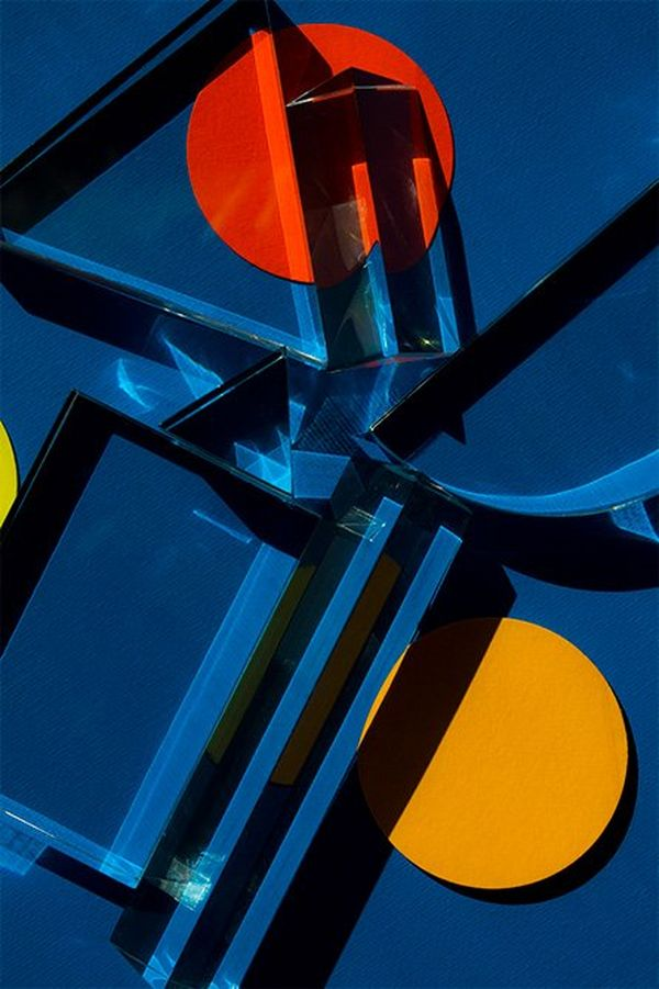 A close-up of a mysterious, brightly-coloured object with circles and sharp edges casting shadows. The colours are mainly rich blue with red and yellow circles.