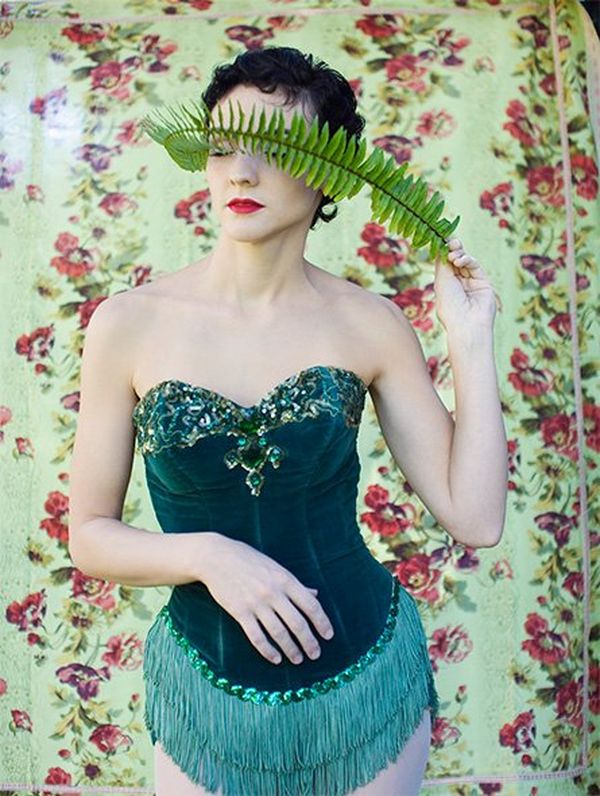 A woman in an emerald-coloured velvet corset trimmed with tassels and beads holds a fern frond across her eyes.