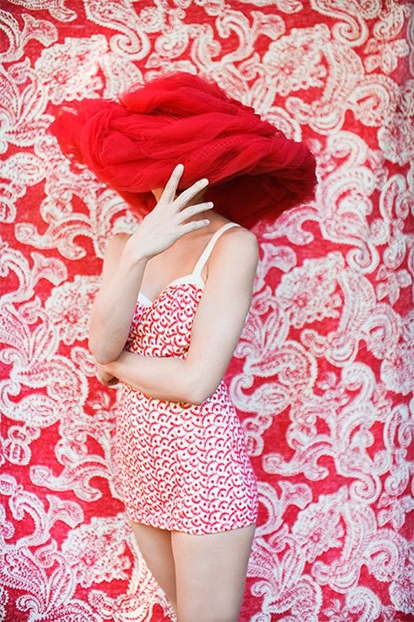 A woman in a red-and-white retro-style swimsuit wears an oversized hat on the head, covering her eyes, and stands in front of a red-and-white patterned wall.