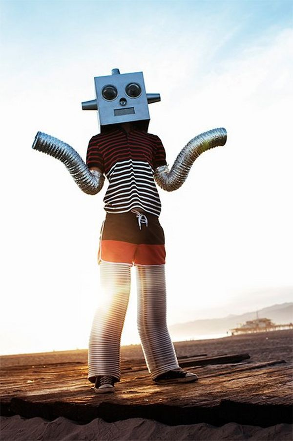 A person dressed as a robot stands on the ground outside, with the sun low on the horizon.