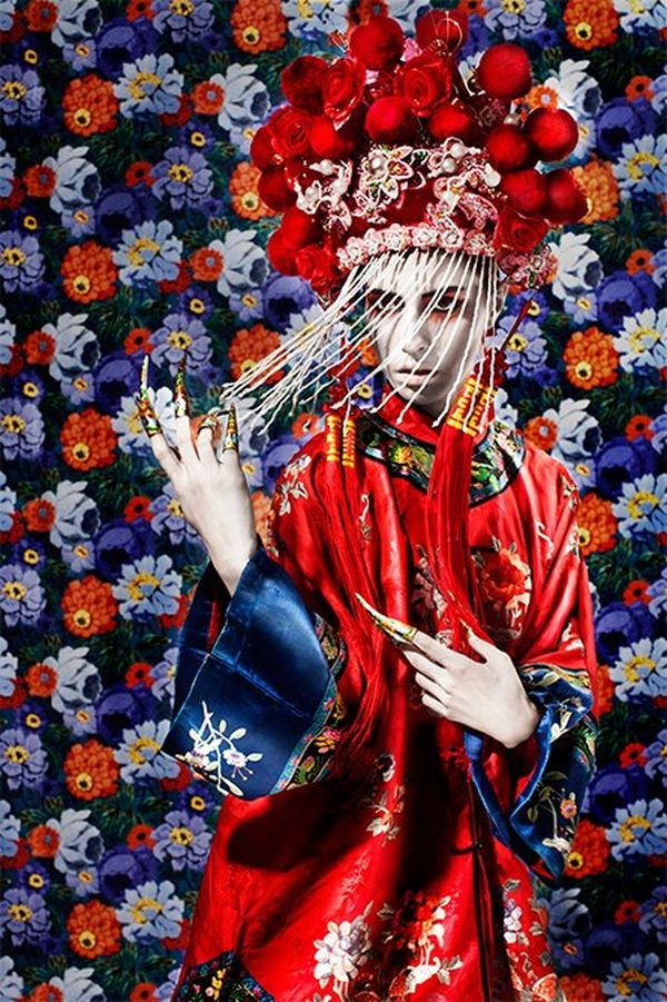 Wearing an ornate red and blue satin kimono and red headdress, a woman stands against a background of richly-coloured flowers.