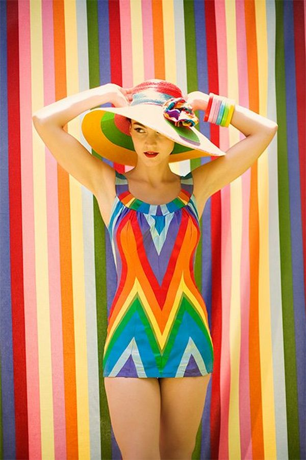 A woman in a rainbow-coloured, stripy, retro-style swimsuit stands against a matching wall, holding a matching sun hat to her head.