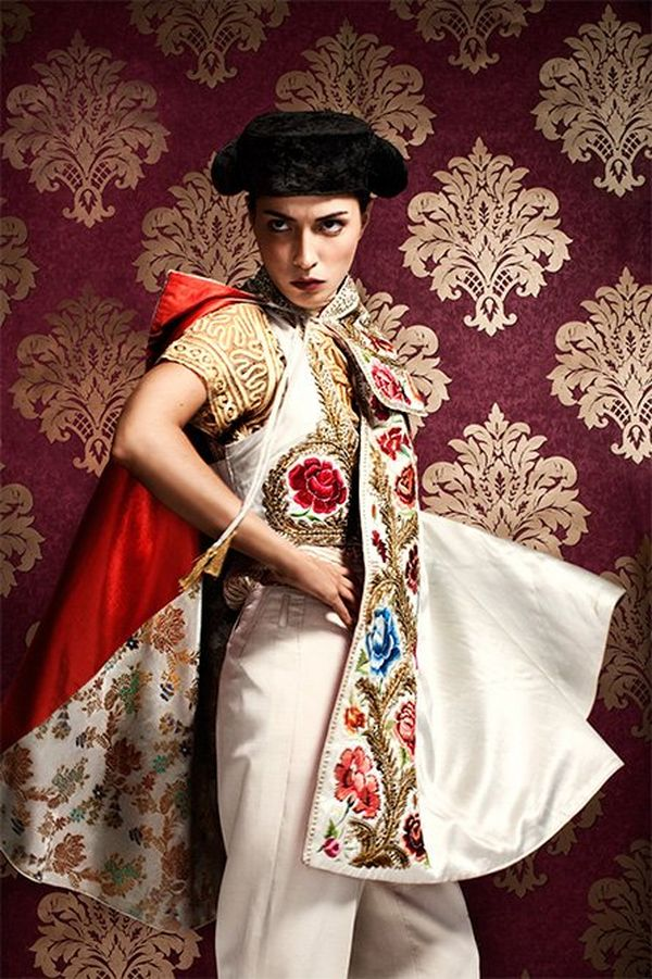 A model is dressed like a matador with ornate satin clothing and hat, standing before a red and gold brocade background.