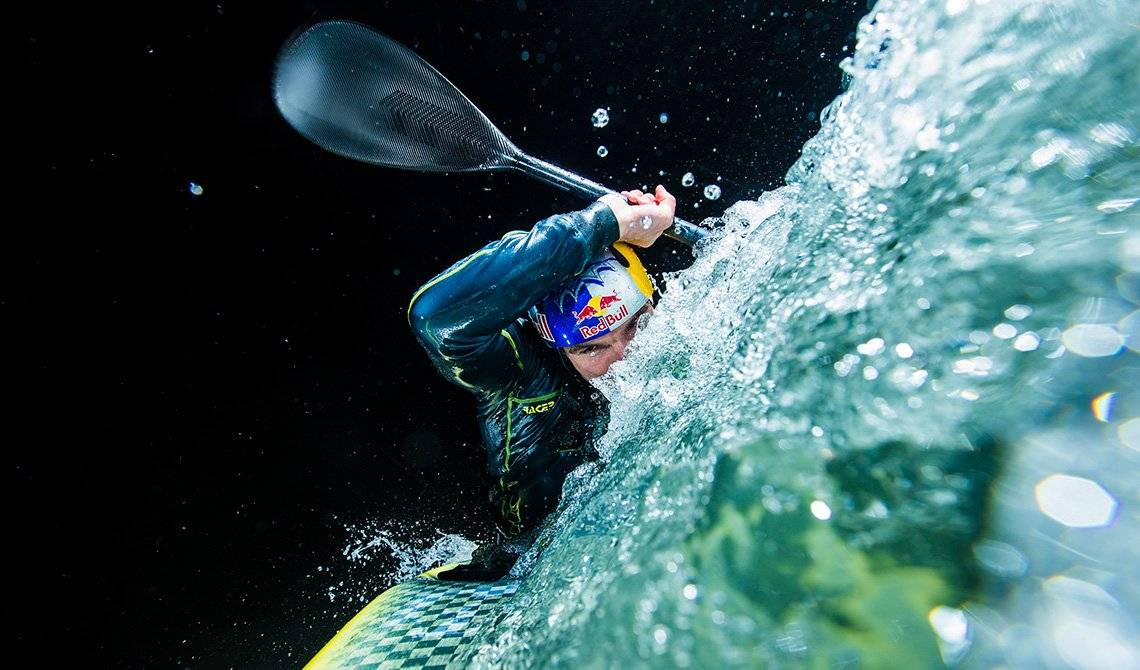 Kayaker Peter Kauzer leans to one side as he paddles through white water, spray highlighted against the night sky.