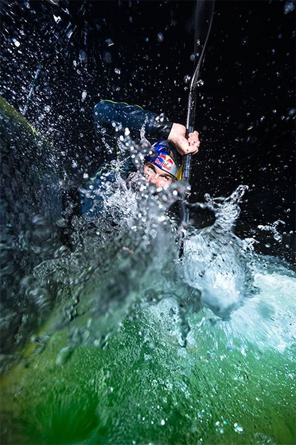 Kayaker Peter Kauzer is almost completely submerged in white water, paddle above his head, at night.