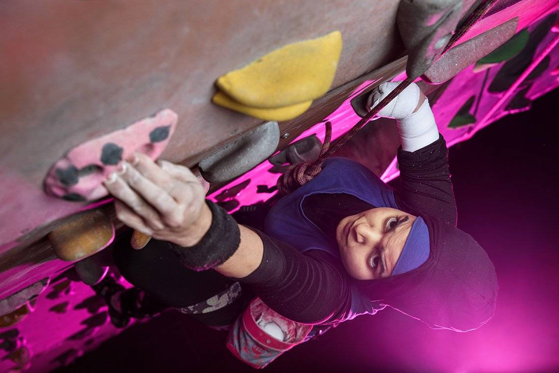 British para climber Anoushé Husain climbs on an indoor climbing wall, lit by a pink light from below.