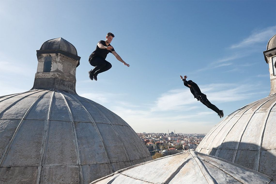 Two men leap in opposite directions on a domed roof in Istanbul.