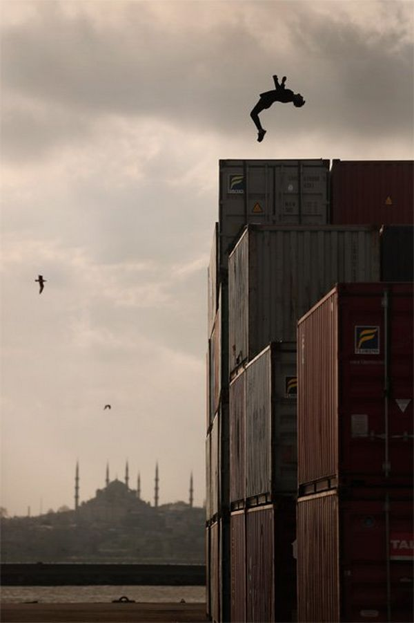A man does a backflip on a stack of shipping containers as the sun sets on the minarets of Istanbul.