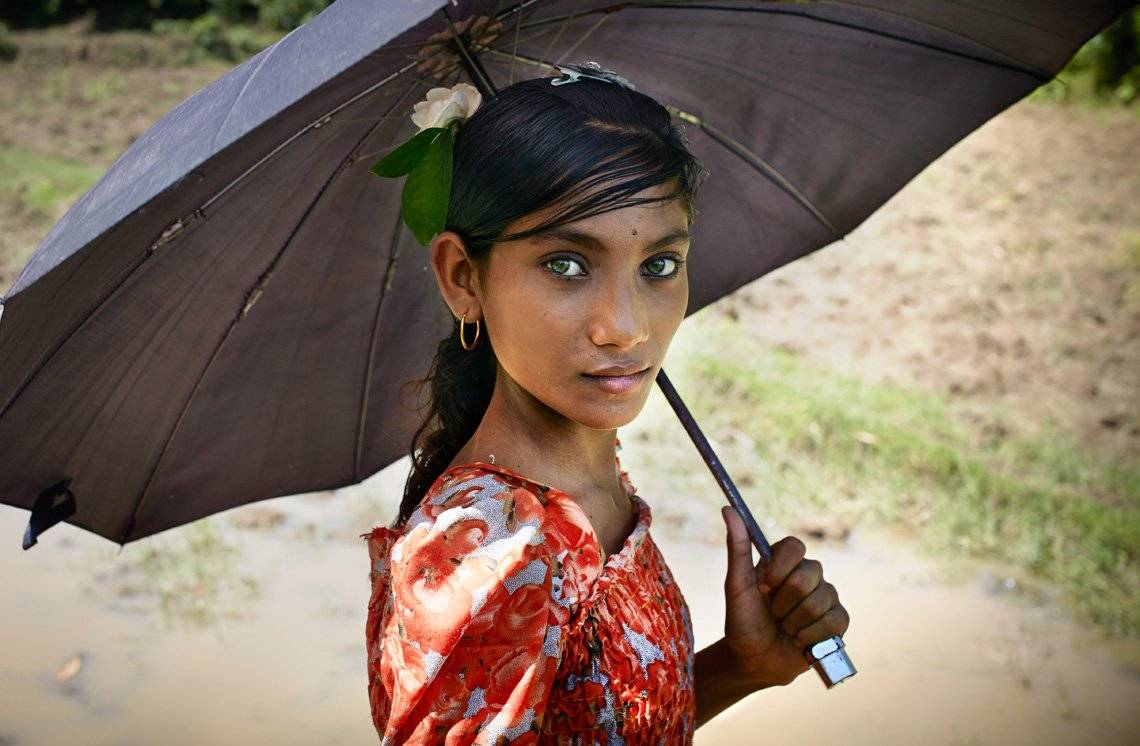 A young girl holding an umbrella stares at the camera.
