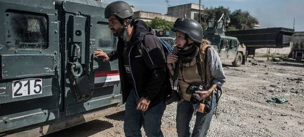 Photojournalist Veronique de Viguerie wears a flak jacket and helmet, her Canon camera flung around her neck, and ducks beside a military vehicle. She is with a man in plain clothes who is also wearing a helmet.