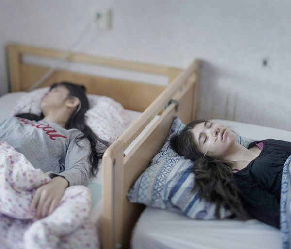 Djeneta (right) and Ibadeta are Roma refugees from Kosovo, now in Horndal, Sweden. They lie bedridden and unresponsive with uppgivenhetssyndrom (resignation syndrome).