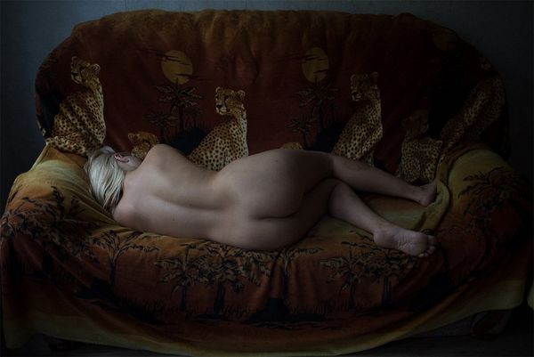 A naked woman lies on her sofa facing away from us.