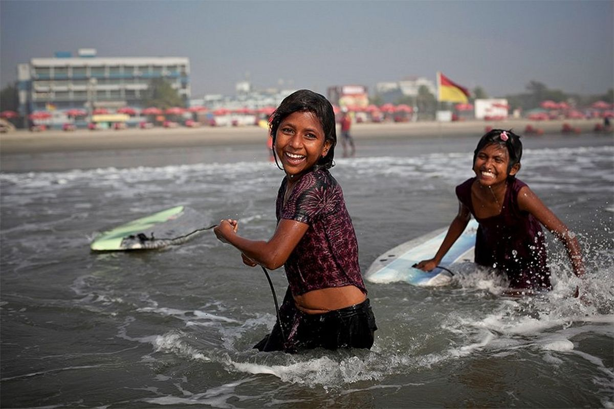 Two 10-year-old Bangladeshi girls smile as they drag their surfboards into the sea, with the beachfront and hotels of Cox's Bazar in the background.