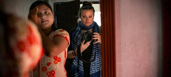 American photographer Allison Joyce takes a photograph of herself in a mirror, holding a Canon DSLR, next to a young Asian girl who is brushing her hair.