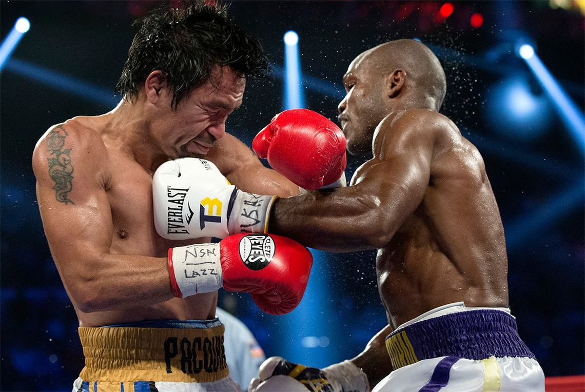 Boxers Manny Pacquiao and Timothy Bradley punch each other in a boxing ring at the MGM Grand.