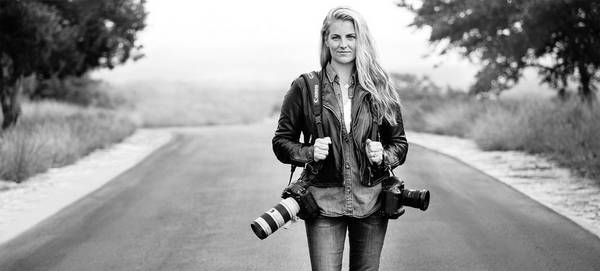 Photographer Elizabeth Kreutz stands in the middle of a road with two Canon cameras over her shoulders.