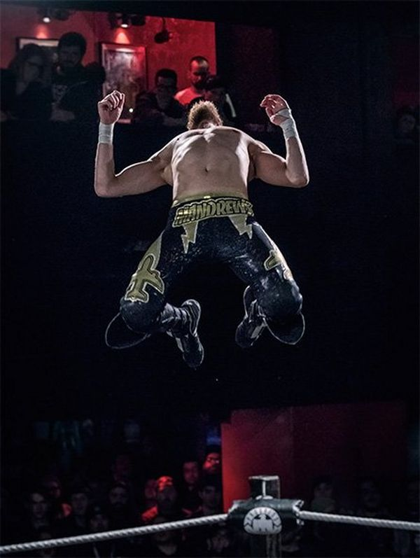 A wrestler jumps high in the air, head back. The crowd look on behind him.