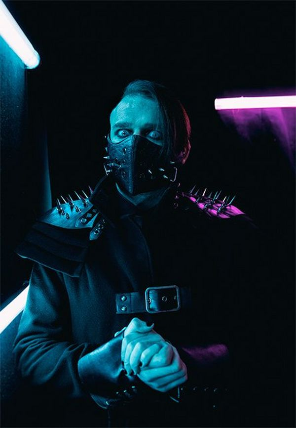 Wrestler Jimmy Havoc wears a studded black leather mask over his mouth, and a black outfit with spiked shoulder pads, as he looks at the camera.
