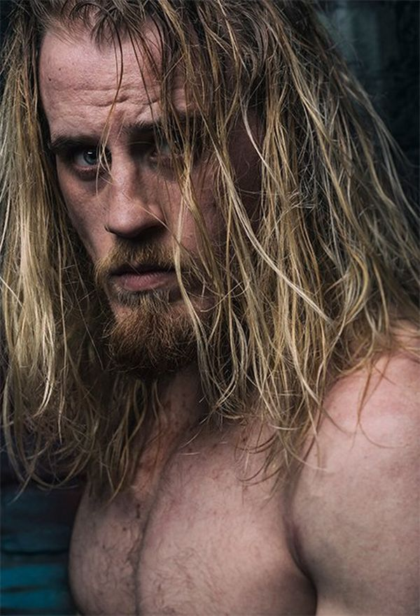 Wrestler Mark Haskins stands by a wooden door, long hair wet with sweat, and looks at the camera.