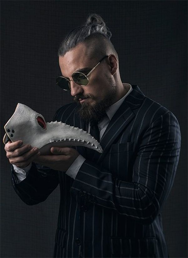 Wrestler Marty Scurll looks at a strange mask resembling an animal's skull with a long beak.