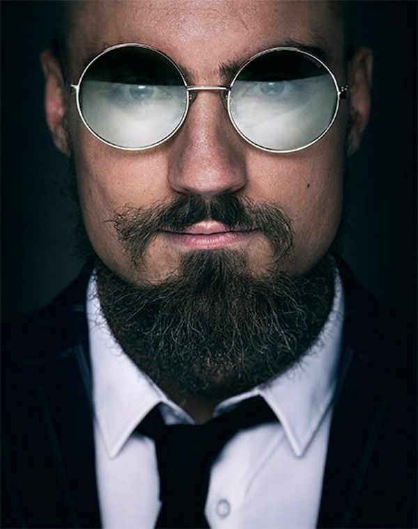 A close-up portrait of wrestler Marty Scurll wearing a suit, tie and round sunglasses, looking at the camera.