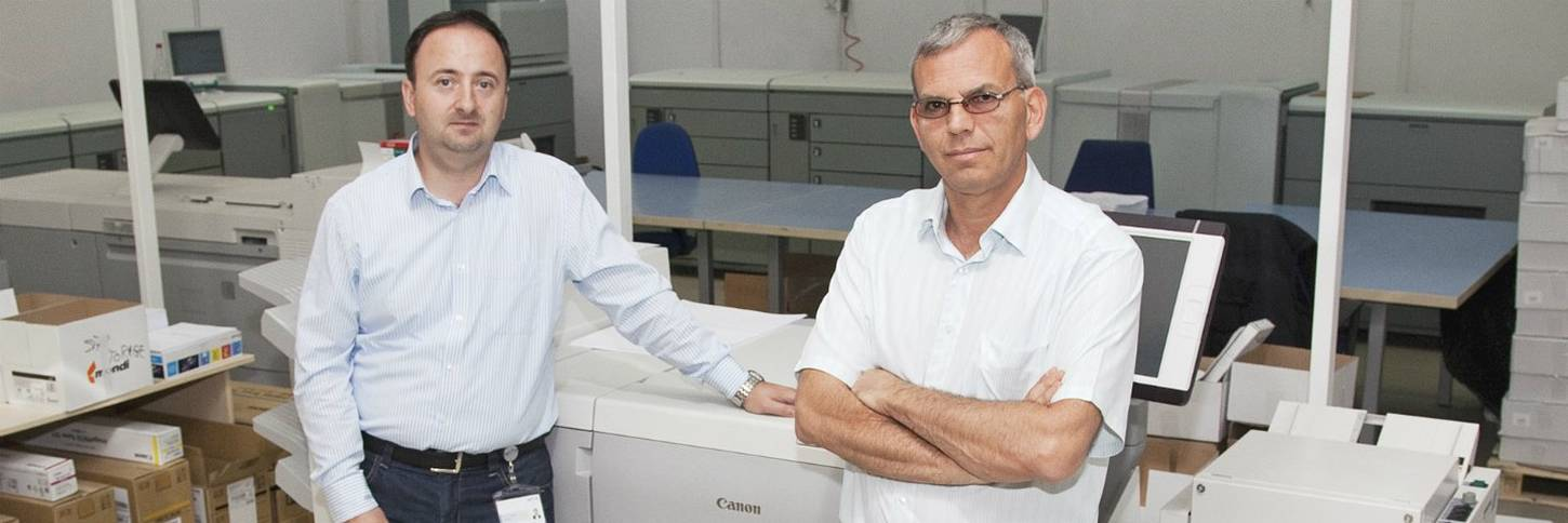 Two men in dark trousers and light shirts stand in front of a large Canon digital printing press.