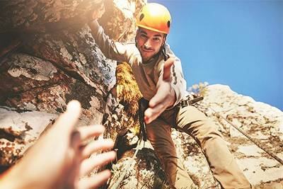 Rock climbing man leans down to take someone's hand